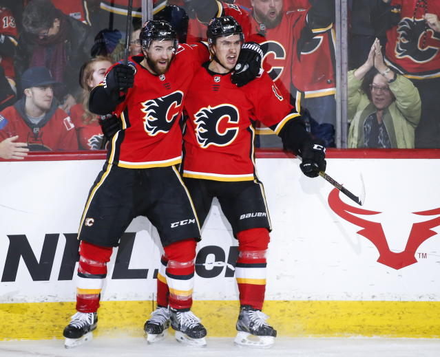 Calgary Flames' Mikael Backlund, right, of Sweden, celebrates his game-winning goal with teammate T.J. Brodie in overtime NHL hockey action against the Carolina Hurricanes, in Calgary, Tuesday, Jan. 22, 2019. (Jeff McIntosh/The Canadian Press via AP)