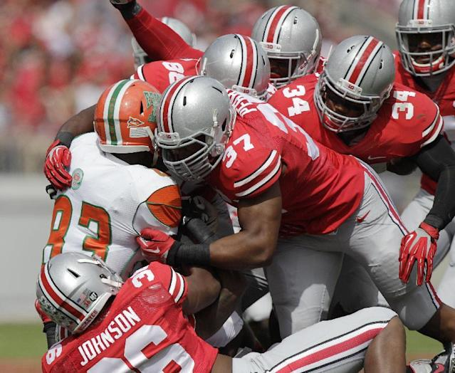 Florida A&M wide receiver Admasen Felix, left, is tackled by Ohio State defenders during the second quarter of an NCAA college football game Saturday, Sept. 21, 2013, in Columbus, Ohio. (AP Photo/Jay LaPrete)
