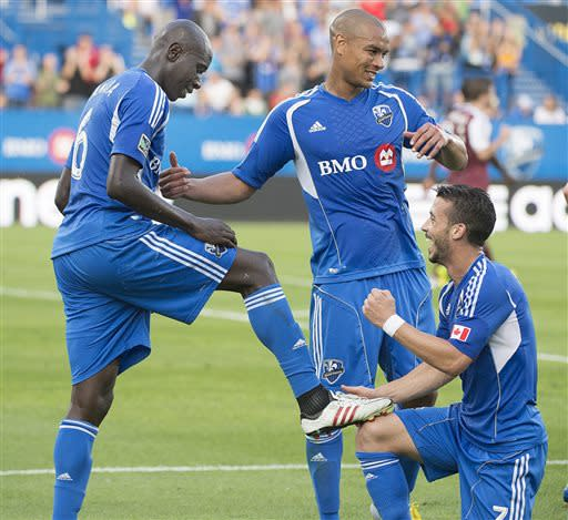 Montreal Impact's Felipe Martins, right, and Sanna Nyassi ,center, celebrate a goal by Hassoun Camara, left, during the first half of an MLS soccer against the Colorado Rapids in Montreal on Saturday, June 29, 2013. (AP Photo/The Canadian Press, Peter McCabe)