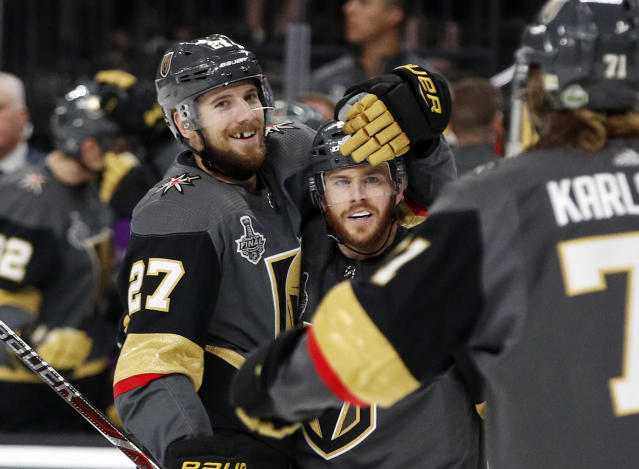 Vegas Golden Knights defenseman Shea Theodore, left, celebrates his goal with center Jonathan Marchessault, center, and center William Karlsson, of Sweden, during the second period in Game 2 of the NHL hockey Stanley Cup Finals against the Washington Capitals on Wednesday, May 30, 2018, in Las Vegas. (AP Photo/John Locher)