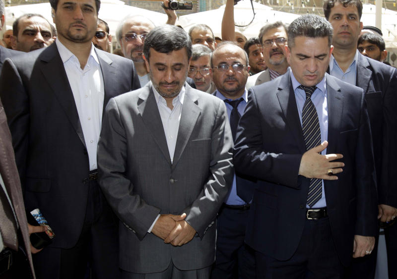 Iranian President Mahmoud Ahmadinejad, center, reacts during his visit to the Imam Ali shrine in Najaf, Iraq, Friday, July 19, 2013. The outgoing Iranian president's visits to the cities of Najaf and Karbala during the Islamic holy month of Ramadan followed meetings with top Iraqi officials in Baghdad on Thursday that highlighted the tightening bonds between Shiite-led Iraq and Iran. (AP Photo/Karim Kadim, Pool)
