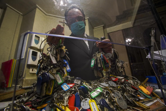 """Gianni Crea, the Vatican Museums chief """"Clavigero"""" key-keeper, sorts out keys as he prepares to open the museum, at the Vatican, Monday, Feb. 1, 2021. Crea is the """"clavigero"""" of the Vatican Museums, the chief key-keeper whose job begins each morning at 5 a.m., opening the doors and turning on the lights through 7 kilometers of one of the world's greatest collections of art and antiquities. The Associated Press followed Crea on his rounds the first day the museum reopened to the public, joining him in the underground """"bunker"""" where the 2,797 keys to the Vatican treasures are kept in wall safes overnight. (AP Photo/Andrew Medichini)"""