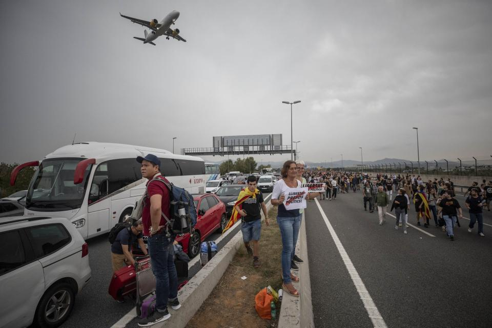 """Protesters block the roads leading to El Prat airport, outskirts of Barcelona, Spain, Monday, Oct. 14, 2019. Spain's Supreme Court on Monday sentenced 12 prominent former Catalan politicians and activists to lengthly prison terms for their roles in a 2017 bid to gain Catalonia's independence, sparking protests across the wealthy Spanish region. The banners in the center read in Catalan """"Freedom Political Prisoners"""" (AP Photo/Bernat Armangue)"""