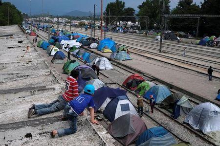 Boys look at tents from a roof of a train station at a makeshift camp for migrants and refugees at the Greek-Macedonian border near the village of Idomeni, Greece, May 10, 2016. REUTERS/Marko Djurica
