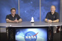 In this frame grab from NASA TV video, astronauts Bob Behnken, left, and Doug Hurley laugh during a news conference, Tuesday, Aug. 4, 2020, in Houston. The two NASA astronauts returned to Earth on Sunday in a dramatic, retro-style splashdown carried out by Elon Musk's SpaceX company. (NASA TV via AP)