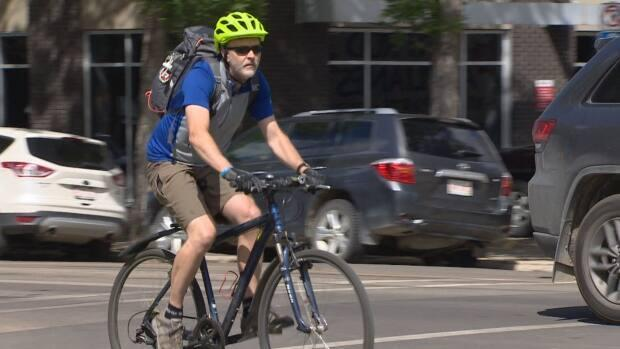 A cyclist rides through downtown Edmonton. Drivers might need to give cyclists at least one metre of space to pass cyclists on city streets if a bylaw is passed. (CBC - image credit)