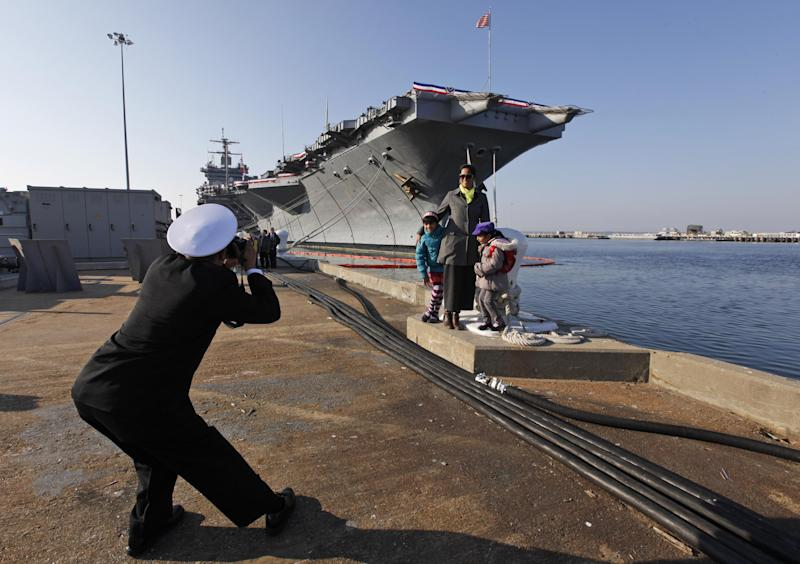 Senior Chief Nageer Rahim, originally from Guyane, photographs his wife, Aliya and their kids in front of the USS Enterprise after an inactivation ceremony for the first nuclear powered aircraft carrier USS Enterprise at Naval Station Norfolk  Saturday, Dec. 1, 2012 in Norfolk, VA.   The ship served in the fleet for 51 years.  (AP Photo/Steve Helber)