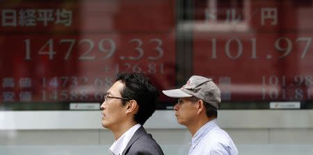 Men walk past electronic boards outside a brokerage in Tokyo