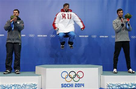 Winner Russia's Alexander Tretiakov (C) jumps on the podium between second-placed Latvia's Martins Dukurs (L) and third-placed Matthew Antoine of the U.S. after the men's skeleton event at the 2014 Sochi Winter Olympics, at the Sanki Sliding Center in Rosa Khutor February 15, 2014. REUTERS/Murad Sezer