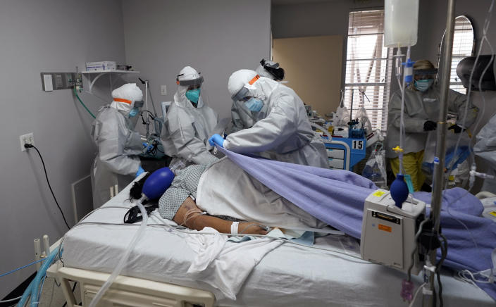 FILE - In this July 6, 2020, file photo, blanket is pulled to cover the body of a patient after medical personnel were unable to to save her life inside the coronavirus unit at United Memorial Medical Center in Houston. The U.S. death toll from COVID-19 has topped 500,000 — a number so staggering that a top health researchers says it is hard to imagine an American who hasn't lost a relative or doesn't know someone who died. (AP Photo/David J. Phillip, File)