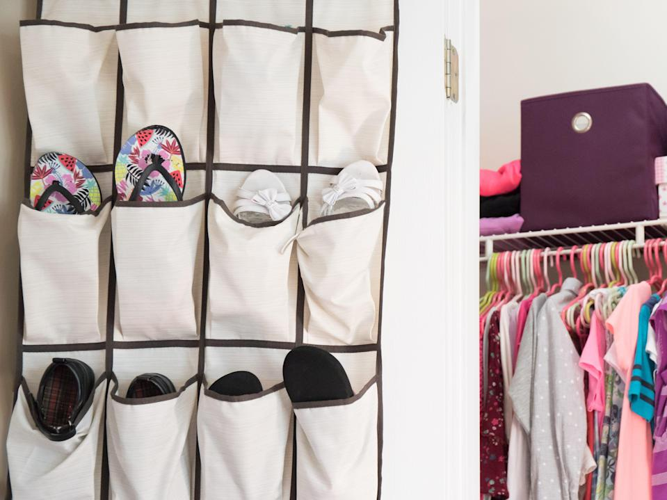 A young girl's closet neatly organized with hanging shoe rack, bins, and boxes