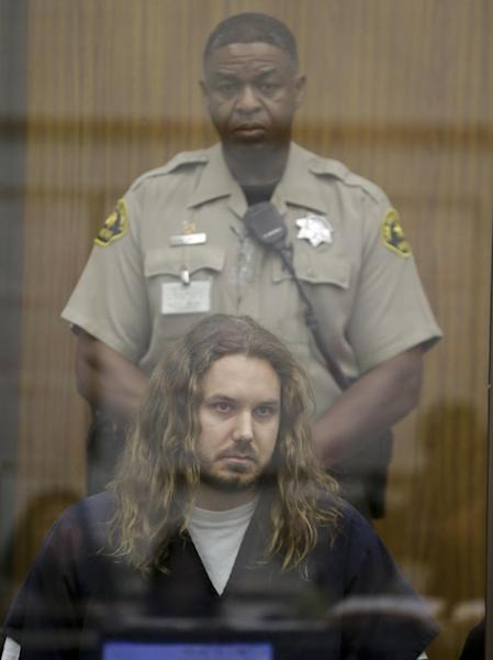 Tim Lambesis, the lead singer for the Metal band As I Lay Dying, sits in a holding area with a San Diego County sheriff deputy in Superior Court awaiting the start of his arraignment on charges he allegedly attempted to hire a hit man to kill his wife in Vista, Calif. Thursday, May 9, 2013. Lambesis was charged late Wednesday with one felony count of solicitation of murder, San Diego County district attorney spokeswoman Tanya Sierra said. (AP Photo/Lenny Ignelzi, Pool)