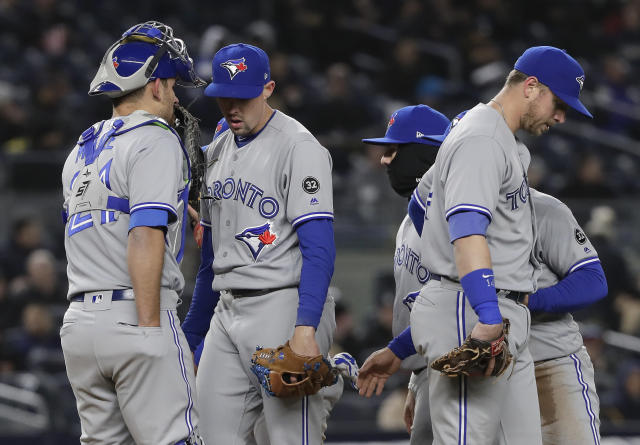 Toronto Blue Jays pitcher Aaron Sanchez, second from left, talks with catcher Luke Maile (21) on the mound during the fifth inning of a baseball game against the New York Yankees, Thursday, April 19, 2018, in New York. (AP Photo/Julie Jacobson)