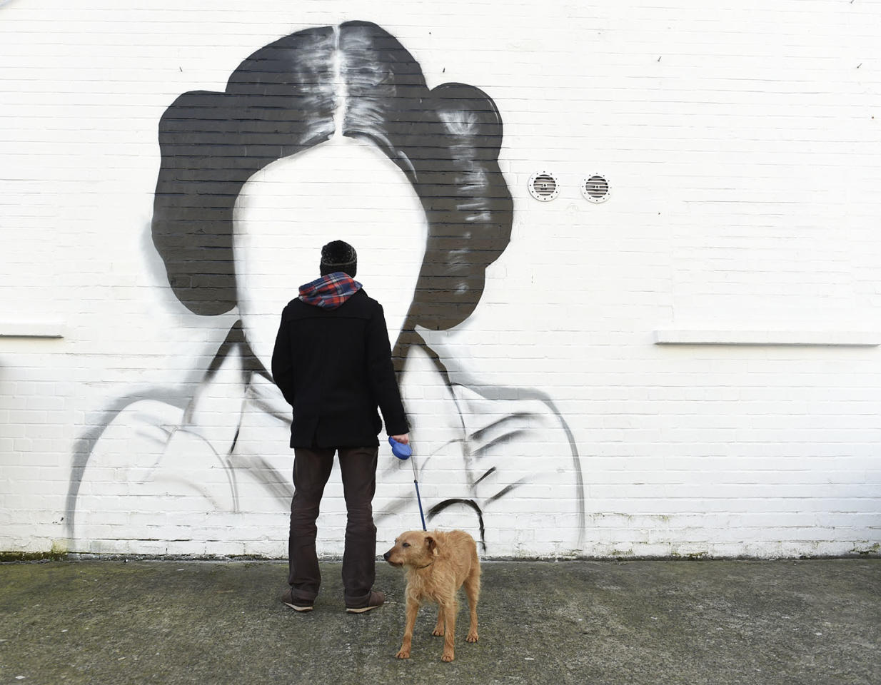 <p>A man and his dog stop to look at a mural depicting Princess Leia from <i>Star Wars</i>, played by Carrie Fisher, in Belfast, Northern Ireland, Jan. 11, 2017. (Photo: Clodagh Kilcoyne/Reuters) </p>