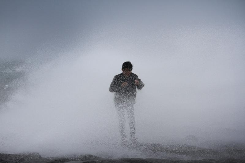 A resident stands near waves in Legazpi City, southeast of Manila, on July 15, 2014 as authorities warned of approaching Typhoon Rammasun (AFP Photo/Charism SAYAT)