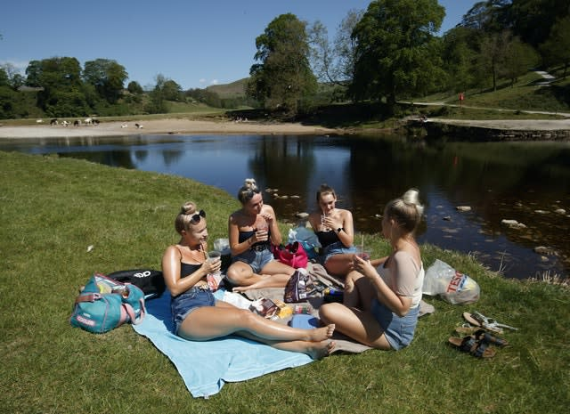 (Left to right) Kate Wormald, Lizzie Walker, Fiona Oddy and Millie Arnison enjoy the hot weather at Bolton Abbey in North Yorkshire