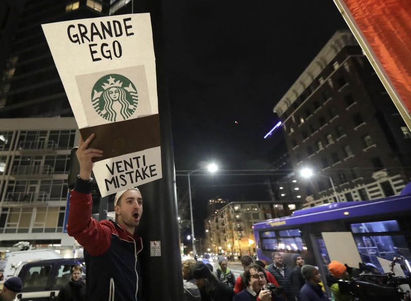 A demonstrator takes part in a protest outside a book promotion event for former Starbucks CEO Howard Schultz