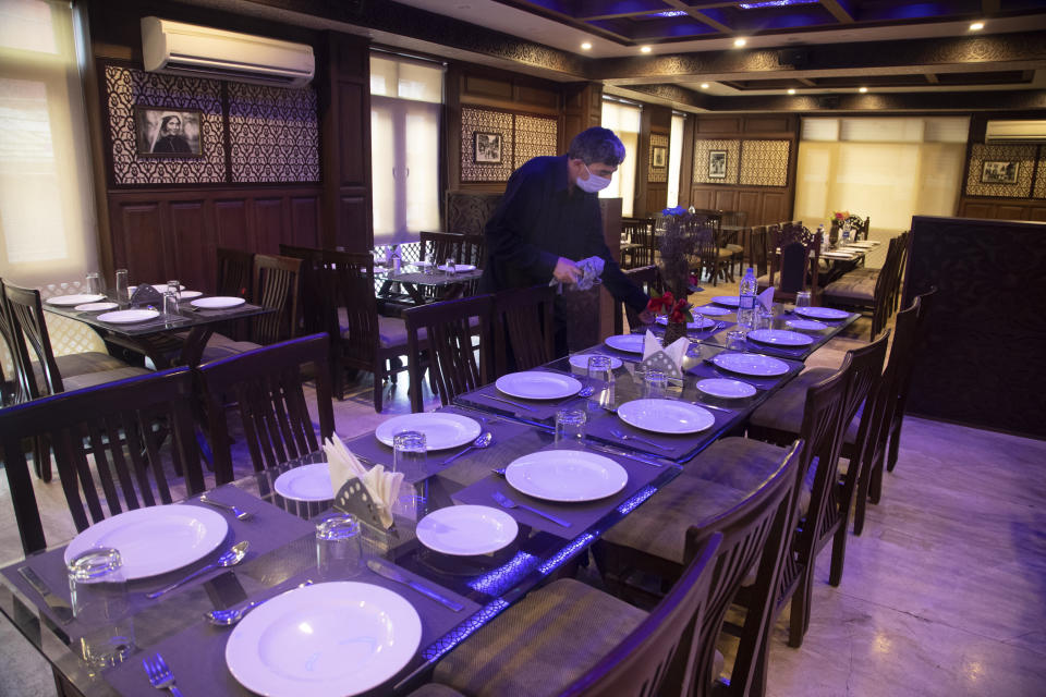 A Kashmiri waiter cleans a table inside a restaurant of Hotel Standard during lockdown to stop the spread of the coronavirus in Srinagar, Indian controlled Kashmir, July 15, 2020. The only activity inside this once-bustling place is now by the cleaning staff. Indian-controlled Kashmir's economy is yet to recover from a colossal loss a year after New Delhi scrapped the disputed region's autonomous status and divided it into two federally governed territories. (AP Photo/Mukhtar Khan)