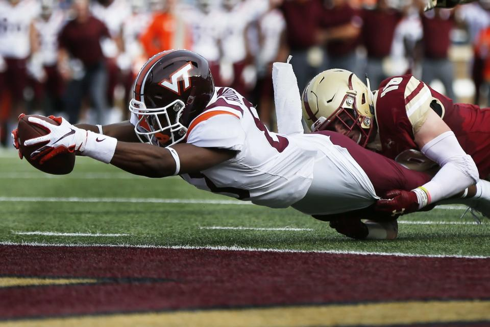 Virginia Tech wide receiver Tayvion Robinson, left, scores against Boston College defensive back Mike Palmer, right, during the first half of an NCAA college football game in Boston, Saturday, Aug. 31, 2019. (AP Photo/Michael Dwyer)