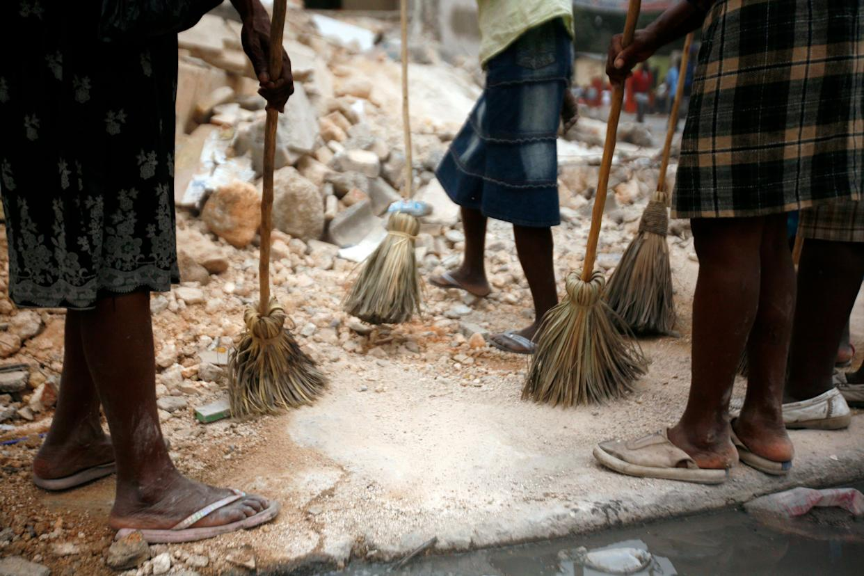 """Women clean the rubble and streets of the Carrefour Feuille area of Port-au-Prince on Jan. 26, 2010, as part of aUnited Nations-supported""""Cash for Work"""" program."""
