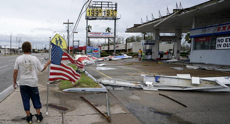 A man stands near debris at a gas station in Lake Charles, Louisiana, after Hurricane Laura moved through the state. Source: AP