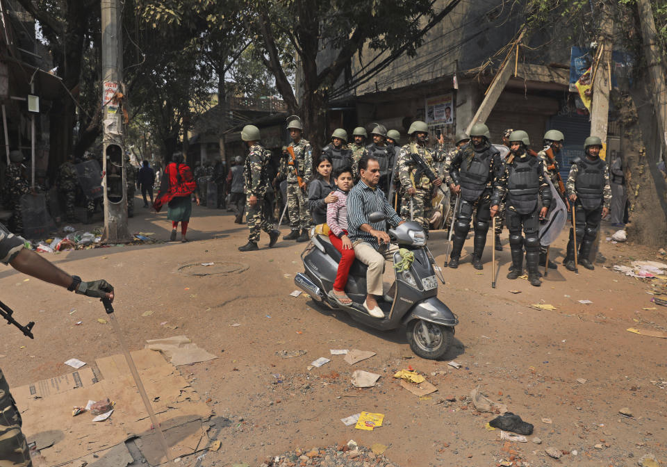 Indian paramilitary soldiers stand guard, as people ride past on a scooter in New Delhi, India, Wednesday, Feb. 26, 2020. At least 20 people were killed in three days of clashes in New Delhi, with the death toll expected to rise as hospitals were overflowed with dozens of injured people, authorities said Wednesday. The clashes between Hindu mobs and Muslims protesting a contentious new citizenship law that fast-tracks naturalization for foreign-born religious minorities of all major faiths in South Asia except Islam escalated Tuesday. (AP Photo/Manish Swarup)