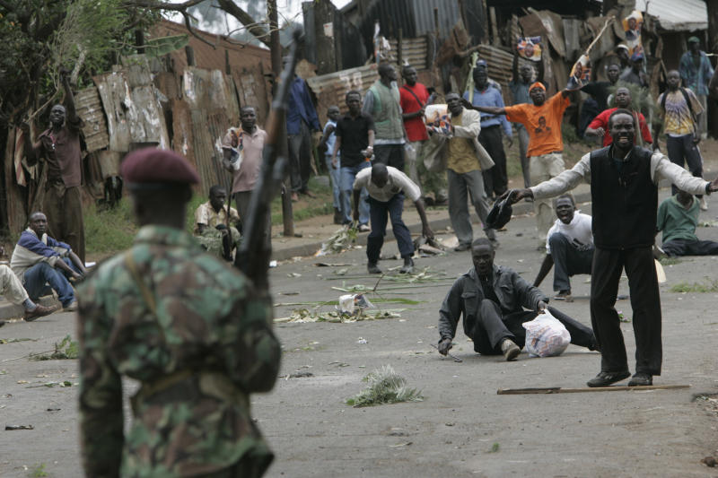 FILE - In this Monday, Dec. 31, 2007 file photo, opposition supporters taunt armed police during post-election riots in the Kibera slum of Nairobi, Kenya. The families of seven people shot dead five years ago and eight wounded survivors this week filed a lawsuit to sue the Kenyan government over police brutality in the violence that followed the country's 2007 election, which comes as Kenya prepares for a new election on March 4, 2013 amid warnings from international human rights groups that the police are not ready to prevent electoral violence while refraining from human rights violations. (AP Photo/Karel Prinsloo, File)