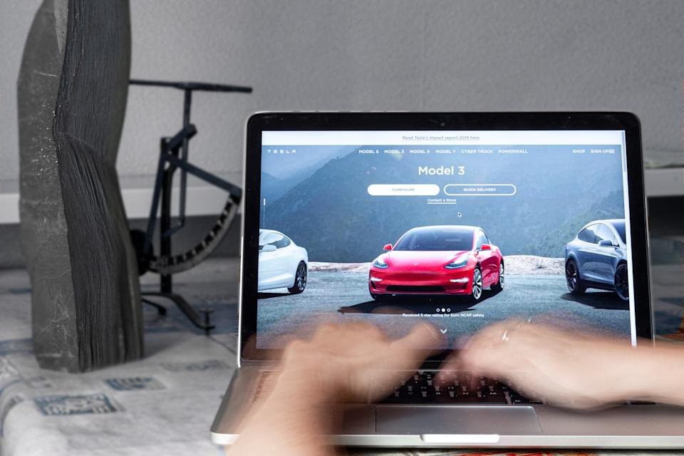 For illustrative purposes a woman woks on a computer in front of Tesla website as Tesla experiences an unexpected increase in sales and profits, despite the automobile industry in general going through major difficulties due to global spread of Coronavirus, London, England July 23, 2020. (Photo Illustration by Dominika Zarzycka/NurPhoto via Getty Images)