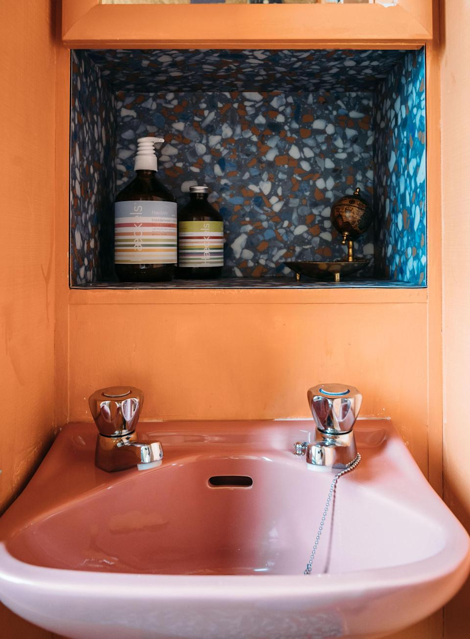 """AFTER: """"I call this the tutti-frutti room,"""" says Anna. The original cabinets and wallpaper were painted orange, while the washbasin and toilet were replaced with another set of bathroom fixtures in baby pink and blue. The small alcove was covered in terrazzo Marmoleum, and one of the walls is now a pinboard for polaroids and postcards."""