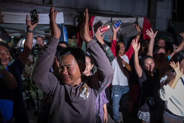 <p>Onlookers at Chiangrai Prachanukroh Hospital cheer as ambulances transport the last rescued schoolboys and their coach from a helipad to the hospital on July 10, 2018, in Chiang Rai, Thailand. Videos released by the Thai navy SEALs showed the boys, ages 11 to 16, and their 25-year-old coach are in good health. (Photo: Linh Pham/Getty Images) </p>