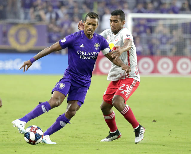Orlando City's Nani, left, passes the ball around New York Red Bulls' Cristian Casseres Jr (23) during the first half of an MLS soccer match, Sunday, July 21, 2019, in Orlando, Fla. (AP Photo/John Raoux)