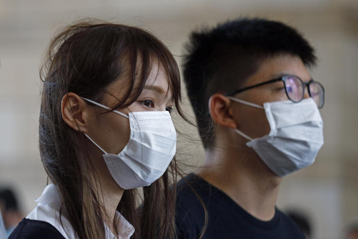 FILE - In this Wednesday, Aug. 5, 2020 file photo, activists Agnes Chow, left, and Joshua Wong arrive at a court in Hong Kong. Police arrested prominent pro-democracy activist Agnes Chow Ting at her home, on charges of inciting secession under the national security law, according to tweets by fellow activist Nathan Law, who is currently in Britain. A post on Chow's official Facebook page said police had arrived at her home and that her lawyers were rushing to the scene. (AP Photo/Kin Cheung, File)