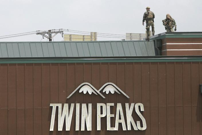 Police officers stand watch from the roof of the Twin Peaks Restaurant in Waco, Texas May 18, 2015. Police braced for retaliation attacks after 170 people were charged on Monday in connection with the shootout among motorcycle gangs a day earlier that left nine dead and 18 wounded at the Twin Peaks restaurant turned into a blood-soaked crime scene. REUTERS/Laura Buckman