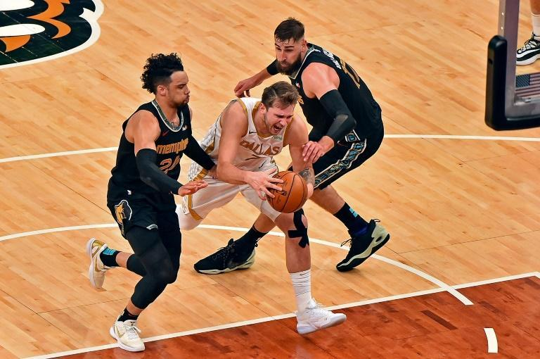 Dallas Maverick Luka Doncic, centre, goes to the basket against Dillon Brooks, left, of the Memphis Grizzlies and Jonas Valanciunas during the second half at FedExForum