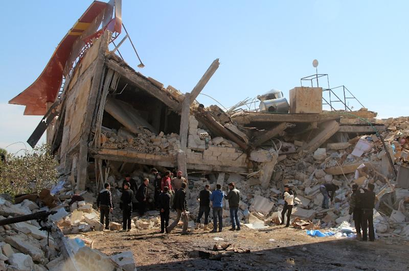 People gathering around the rubble of a hospital supported by Doctors Without Borders (MSF) near Maaret al-Numan, in Syria's northern province of Idlib,  after the building was hit by suspected Russian air strikes
