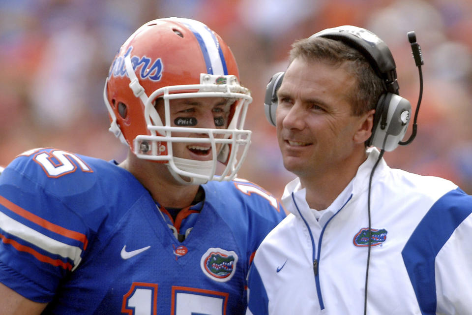 FILE - In this Oct. 25, 2008, file photo, Florida quarterback Tim Tebow (15) shares a laugh with coach Urban Meyer during the fourth quarter of an NCAA college football game against Kentucky in Gainesville, Fla. Tebow and Meyer are together again, this time in the NFL and with Tebow playing a new position. The former Florida star and 2007 Heisman Trophy-winning quarterback signed a one-year contract with the Jacksonville Jaguars on Thursday, May 20, 2021, and will attempt to revive his pro career as a tight end. (AP Photo/Phil Sandlin, File)