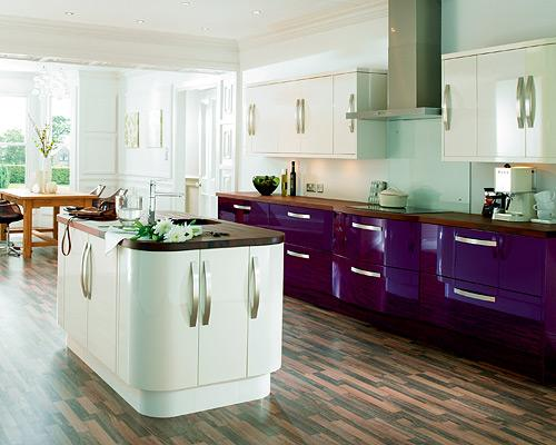 """<b>Aubergine dream</b><br><br>Rounded corner-units have been popular for a while, but this high gloss kitchen from <a href=""""http://www.diy.com/nav/rooms/kitchens/cooke-lewis-kitchens?noCookies=false"""" rel=""""nofollow noopener"""" target=""""_blank"""" data-ylk=""""slk:Cooke & Lewis at B&Q"""" class=""""link rapid-noclick-resp""""><span>Cooke & Lewis at B&Q</span></a> takes streamlined elegance to a new level. <br><br>The bright aubergine base units with curved chrome handles make for a striking, contemporary kitchen. If you love strong colour but have a compact kitchen, keeping the wall cupboards white will prevent the look from becoming too overpowering."""
