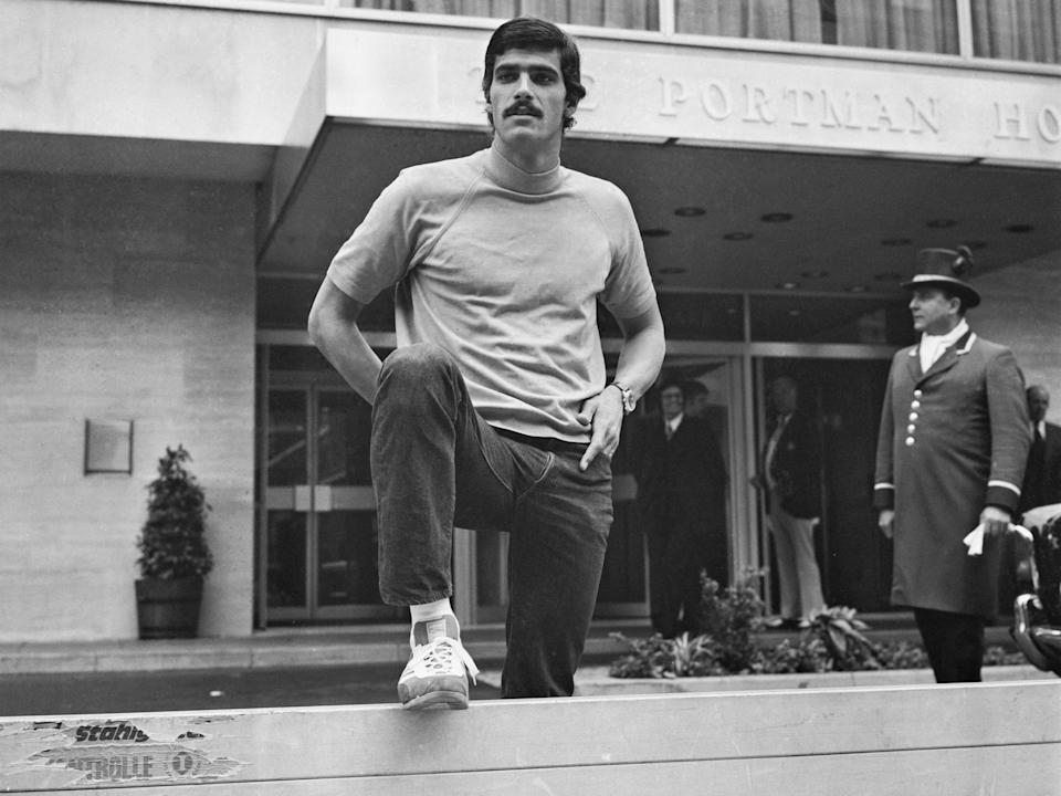 Mark Spitz in sweatsuit with leg up on bar in 1972