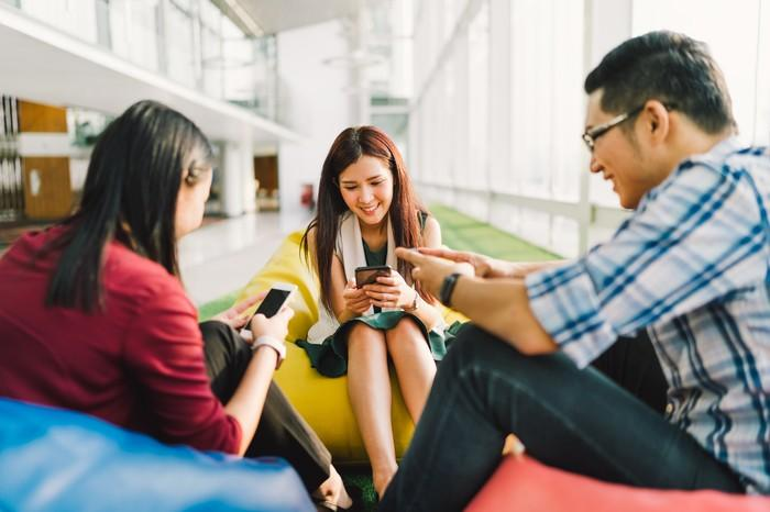 A group of smiling Asian youngsters sitting on bean bags while on their smartphones.
