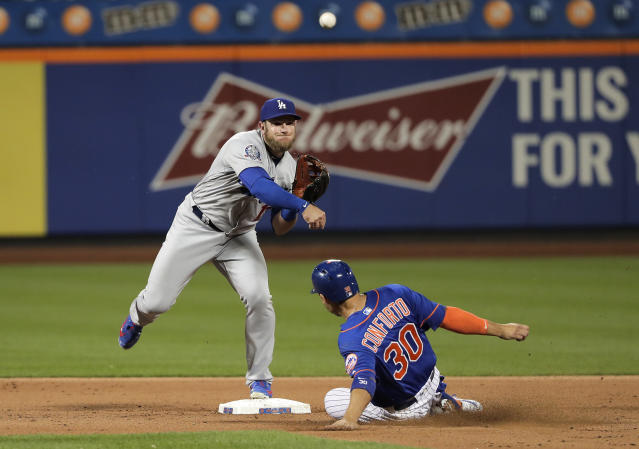 Los Angeles Dodgers second baseman Max Muncy, left, throws to first on a double play as New York Mets' Michael Conforto (30) attempts to break it up during the eighth inning of a baseball game, Friday, June 22, 2018, in New York. Conforto was out at second base and Jose Bautista was out at first. (AP Photo/Julie Jacobson)