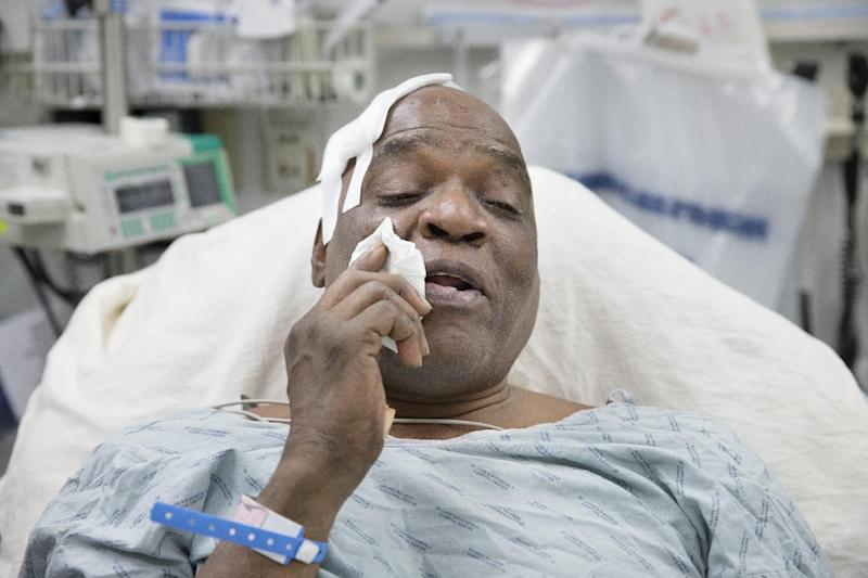 Cecil Williams wipes tears from his face during an interview as he rests in his hospital bed following a fall onto subway tracks from the platform at 145th Street, Tuesday, Dec. 17, 2013, in New York. Williams, 61 and blind says he fainted while holding onto his black Labrador guide dog, Orlando, who tried to save him from falling. (AP Photo/John Minchillo)