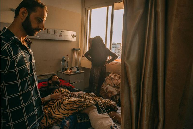 An injured man rests in a bed at Shifa Hospital in Gaza City.