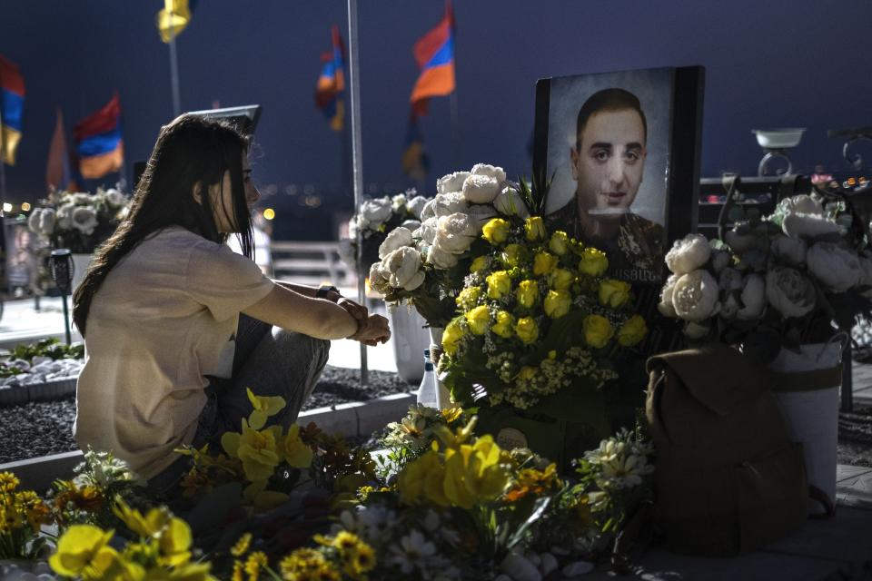 A woman sits at the grave of her brother killed during the fighting over Nagorno-Karabakh in 2020 year, at the military cemetery outside Yerevan, Armenia. June 16. 2021. Nagorno-Karabakh lies within Azerbaijan but was under the control of ethnic Armenian forces backed by the government in Yerevan since a separatist war ended in 1994, leaving the region and substantial surrounding territory in Armenian hands. Hostilities flared in late September 2020, and the Azerbaijani military pushed deep into Nagorno-Karabakh and nearby areas in six weeks of fighting involving heavy artillery and drones that killed more than 6,000 people. (AP Photo/Areg Balayan)