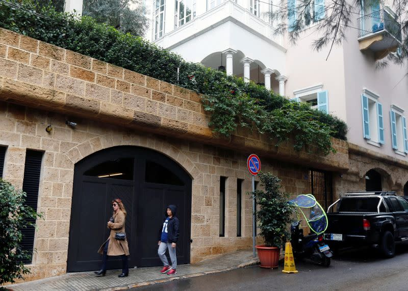 People walk past a house that is believed to belong to Carlos Ghosn in Beirut