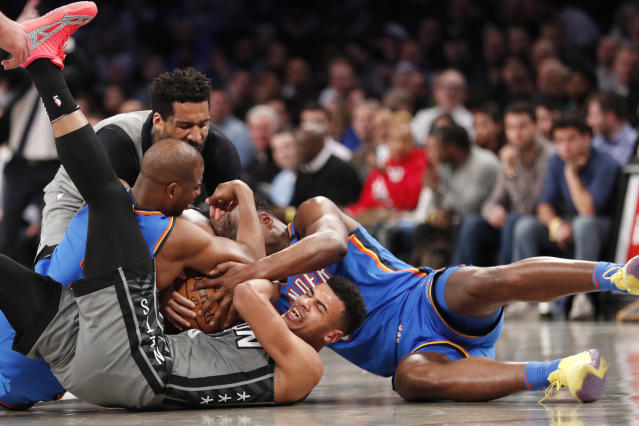 Brooklyn Nets guard Timothe Luwawu-Cabarrot (9) struggles to control the ball a he engages in a floor scramble with Oklahoma City Thunder guard Chris Paul, left, and Thunder guard Deonte Burton (30) during the first half of an NBA basketball game, Tuesday, Jan. 7, 2020, in New York. Nets forward Wilson Chandler, upper left, gets in on the tug-of-war. (AP Photo/Kathy Willens)