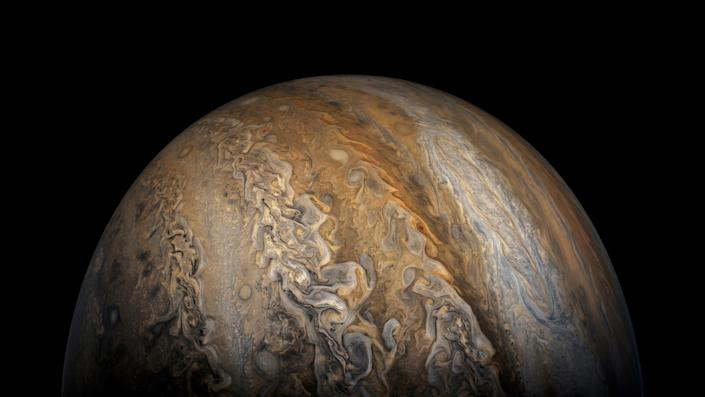 Jupiter planet rising in darkness with swirling orange white purple-brown bands