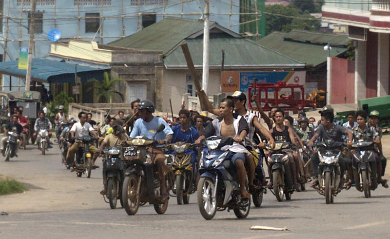 Hundreds of Buddhists on motorcycles armed with sticks patrol in the streets of in Lashio, northern Shan State, Myanmar, Wednesday, May 29, 2013. Sectarian violence spread to a new region of Myanmar, with a mob burning shops in the northeastern town after unconfirmed rumors spread that a Muslim man had set fire to a Buddhist woman. (AP Photo/Gemunu Amarasinghe)