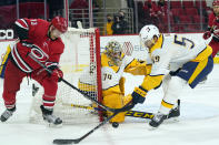 Nashville Predators goaltender Juuse Saros (74) and defenseman Roman Josi (59) defend against Carolina Hurricanes left wing Warren Foegele (13) during the second period of an NHL hockey game in Raleigh, N.C., Saturday, April 17, 2021. (AP Photo/Gerry Broome)