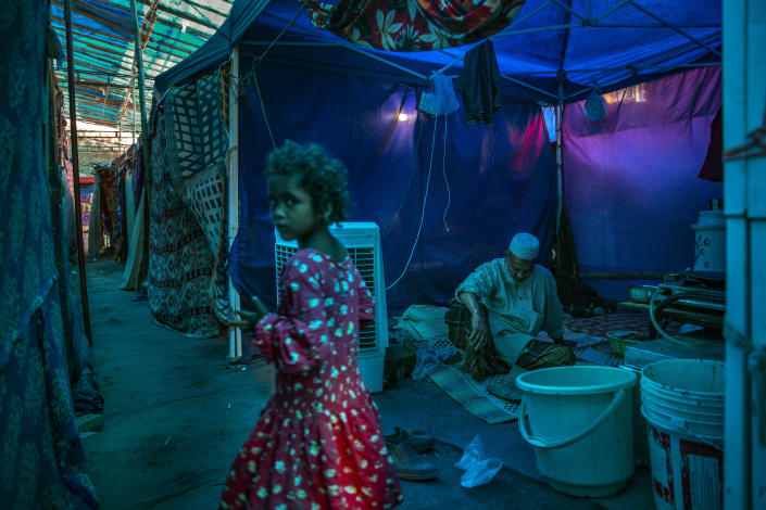 A young Rohingya refugee girl walks past an elderly man sitting inside a tent at a refugee camp alongside the banks of the Yamuna River in the south-eastern borders of New Delhi, sprawling Indian capital, July 1, 2021. Millions of refugees living in crowded camps are waiting for their COVID-19 vaccines. For months, the World Health Organization urged countries to prioritize immunizing refugees, placing them in the second priority group for at-risk people, alongside those with serious health conditions. (AP Photo/Altaf Qadri)