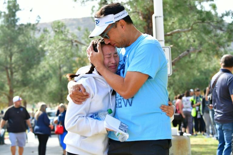 A man embraces his daughter after a shooting at Saugus High School in Santa Clarita, California (AFP Photo/Frederic J. BROWN)